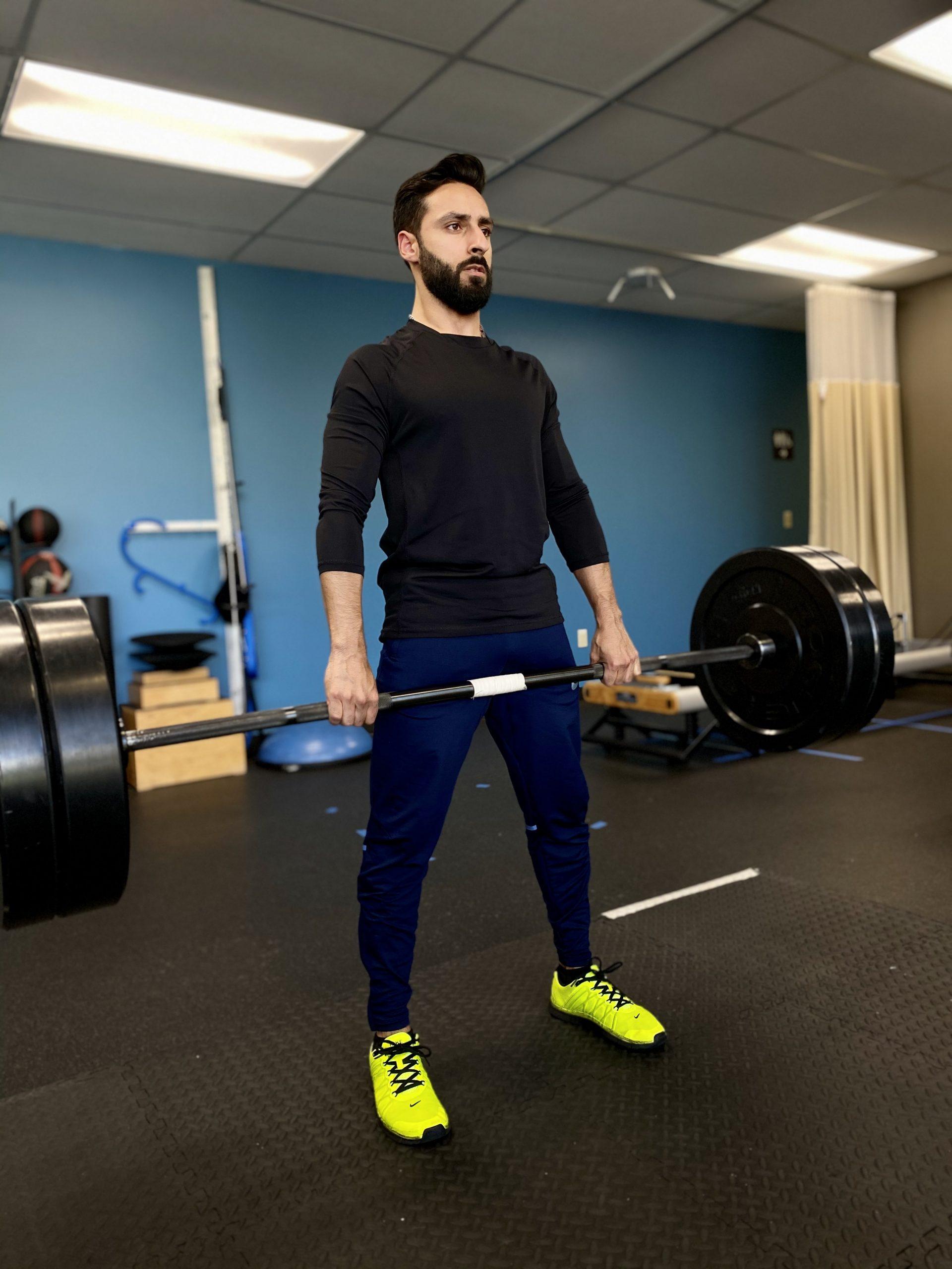 Dr. Ashok Bhandari lifting weights in a gym
